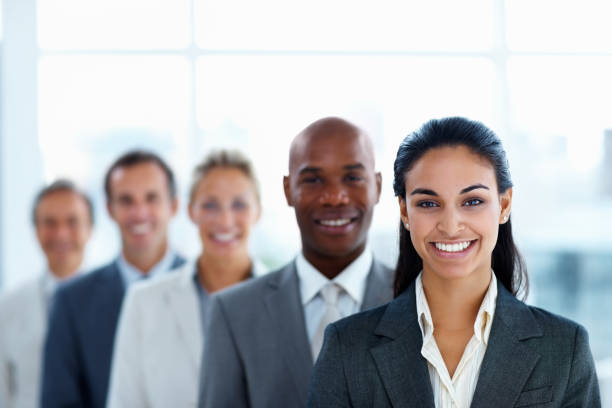 Businesswoman colleagues standing in a line and smiling stock photo