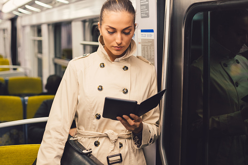 Young woman reading a book in the subway train