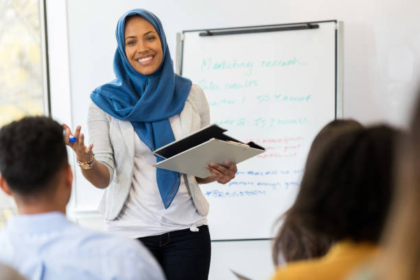 Businesswoman conducts employee training class A mid adult Muslim businesswoman smiles as she speaks to a group of employees during a training class. islam stock pictures, royalty-free photos & images