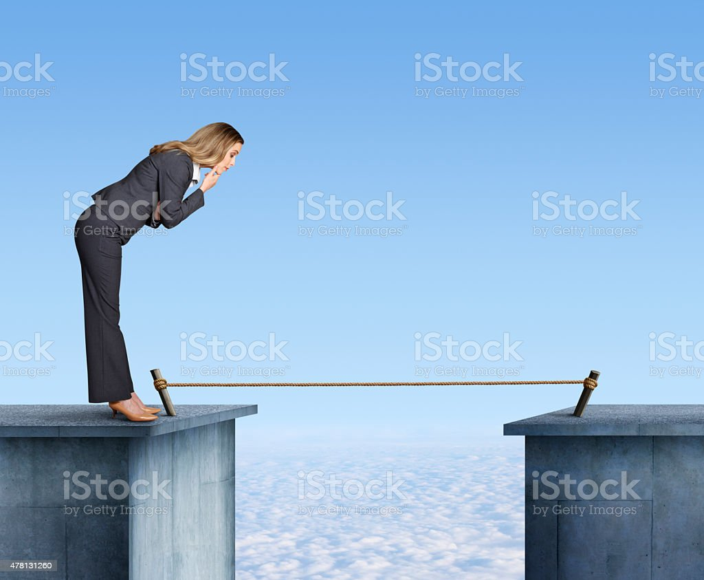 Businesswoman Contemplating Having To Cross A Tightrope stock photo