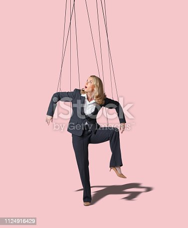 A businesswoman looks up as she is controlled by the strings of a marionette against a pink background.