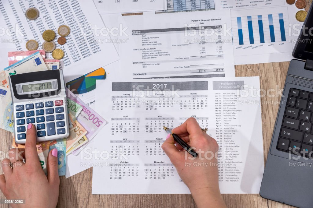 Businesswoman counting on calculator annual home budget and thinking about his cost. stock photo