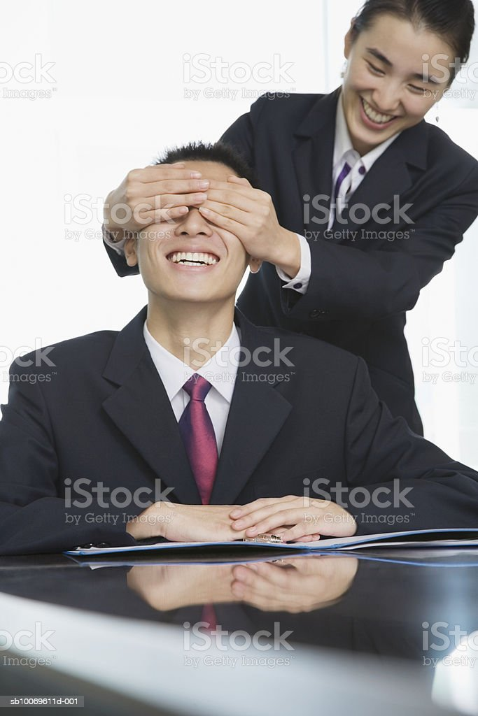 Businesswoman covering businessman's eyes royalty-free stock photo