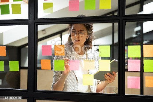 istock Businesswoman creates priority to-do list on sticky notes 1181590449