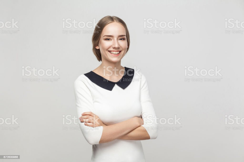 Businesswoman crossed hands, toothy smiling and looking at camera stock photo