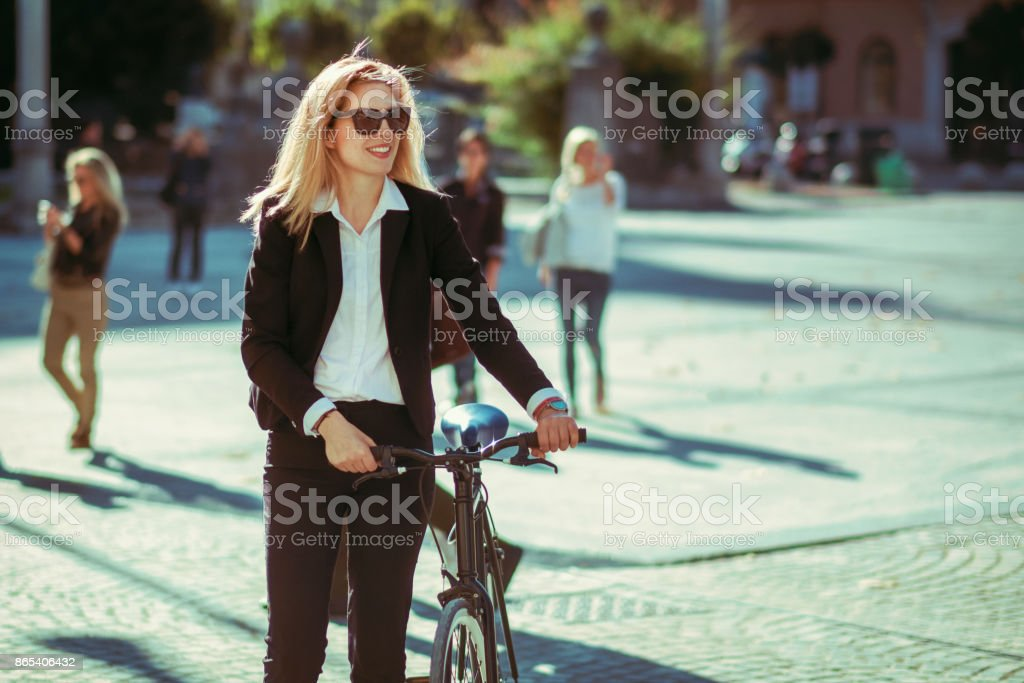 Businesswoman cycling in the city stock photo