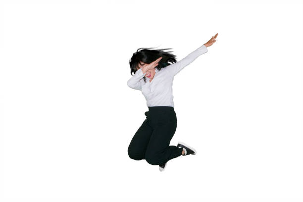Businesswoman dancing and jumping in studio stock photo
