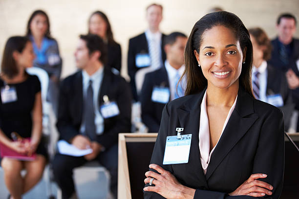 Businesswoman Delivering Presentation At Conference stock photo