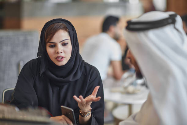 Businesswoman discussing with colleague at office stock photo