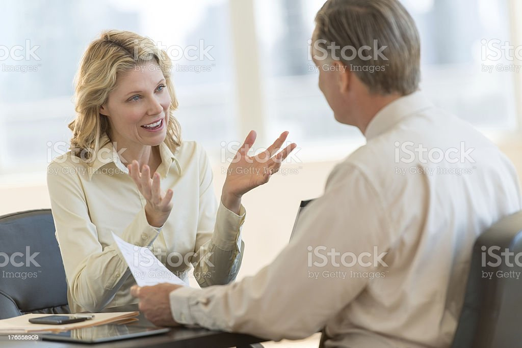Businesswoman Discussing With Colleague In Office stock photo