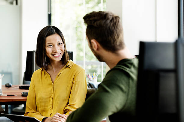 businesswoman discussing with colleague in office - two people stock pictures, royalty-free photos & images