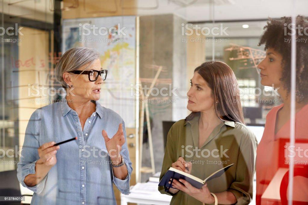 Geschäftsfrau, die Diskussion mit Kollegen am Glas – Foto