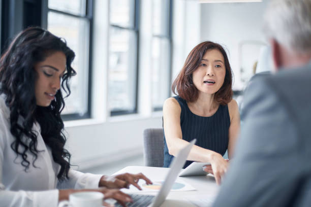 Businesswoman discussing with colleagues at table stock photo