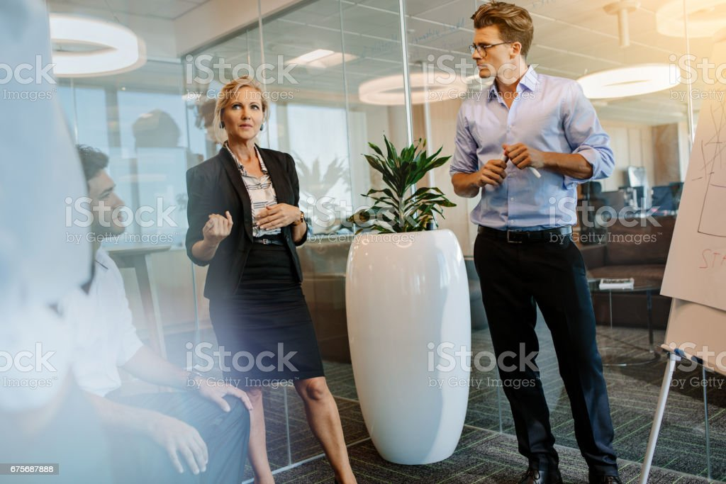 Businesswoman discussing with colleagues during presentation royalty-free stock photo