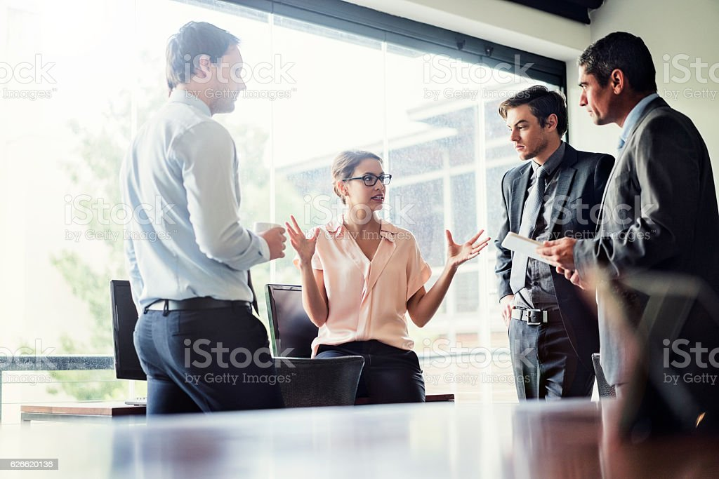Businesswoman discussing with colleagues in office stock photo