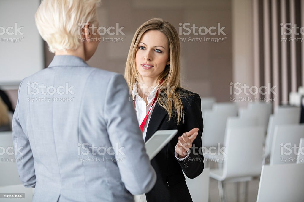 Businesswoman discussing with female colleague in seminar hall stock photo