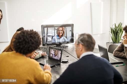 Senior businesswoman discussing with her team through conference call. Mature female professional doing video call with colleagues.