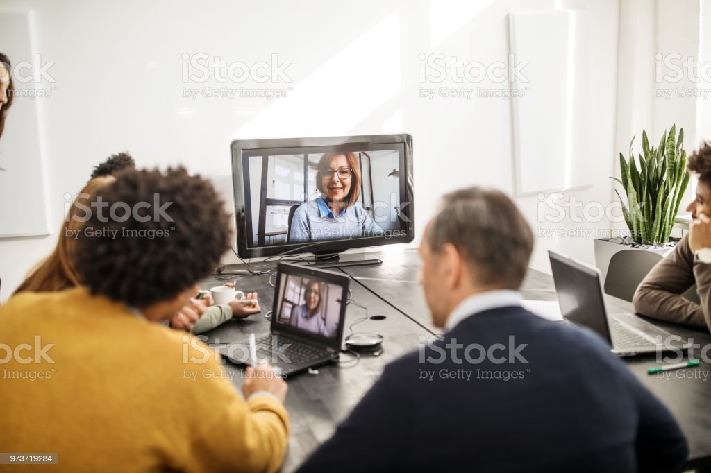 Businesswoman doing conference call with colleagues stock photo