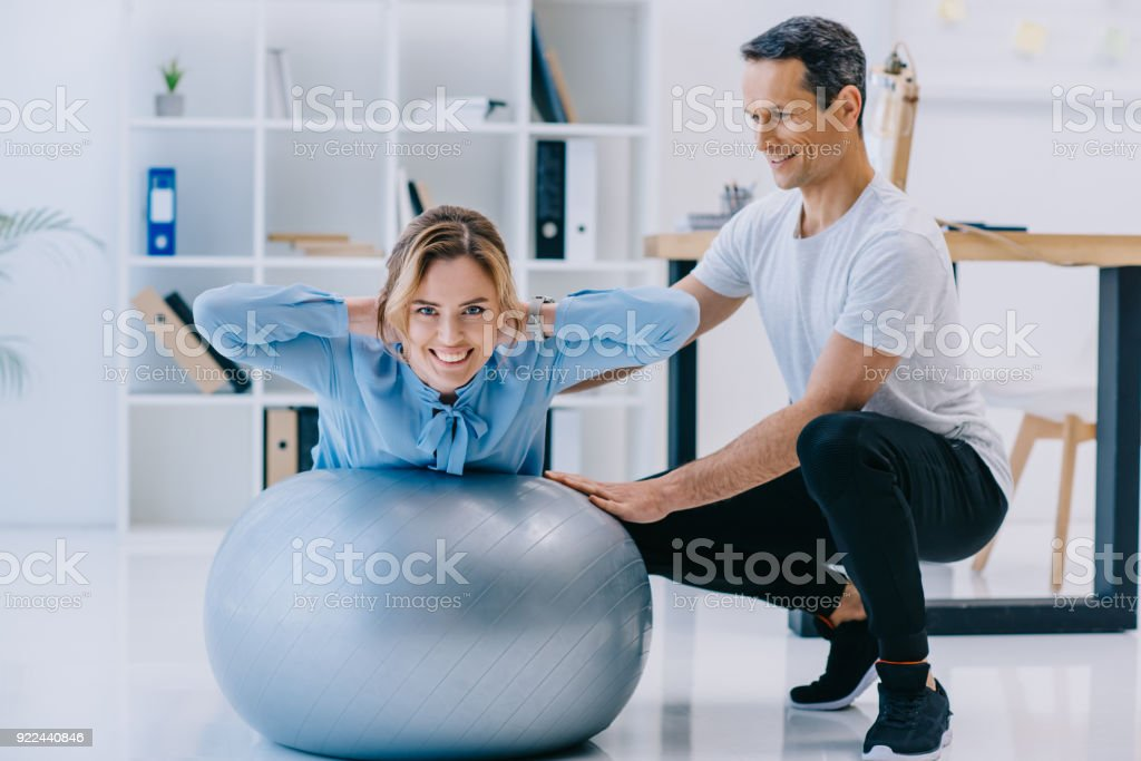 businesswoman doing hyperextension exercise on fit ball with trainer at office stock photo