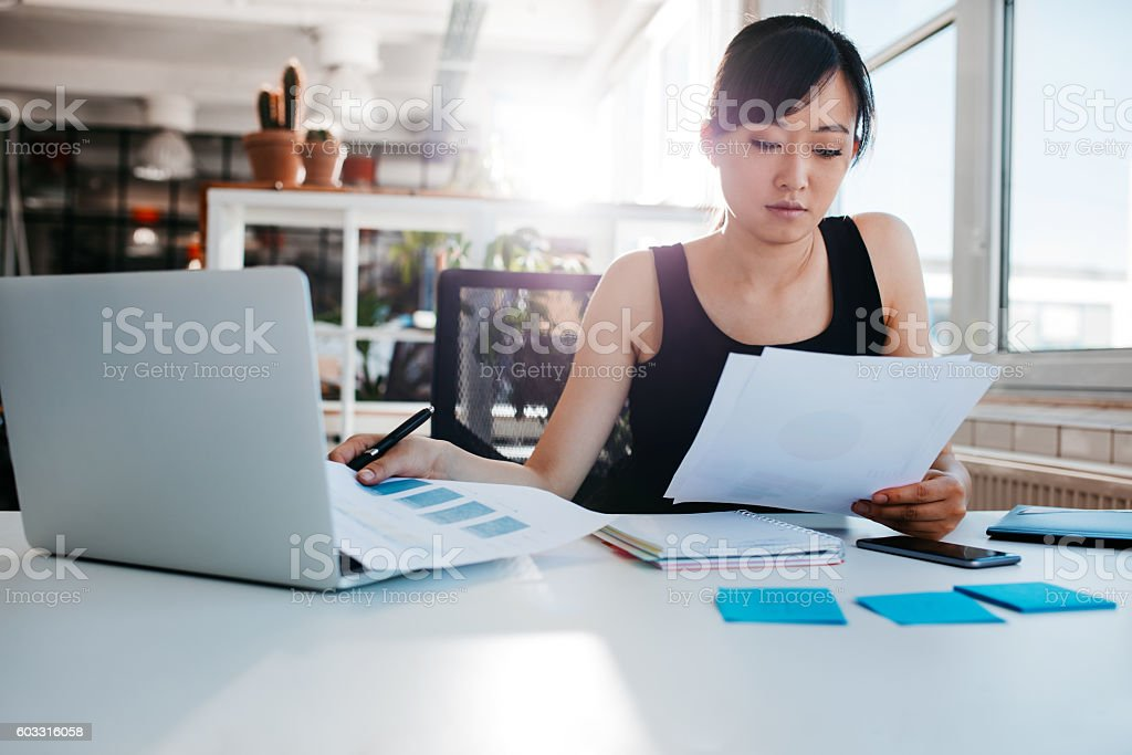 Businesswoman doing paperwork at her workplace stock photo