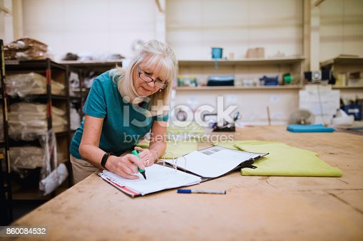 istock Businesswoman Doing Paperwork In Factory 860084532