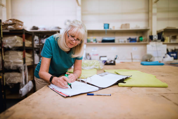 businesswoman doing paperwork in factory - owner stock pictures, royalty-free photos & images