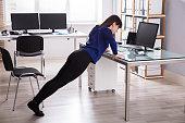 Businesswoman Doing Push Up On Office Desk