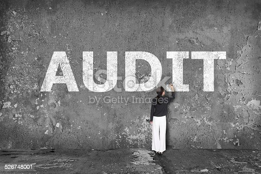531925785 istock photo businesswoman drawing  audit on the wall 526748001