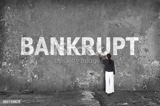 istock businesswoman drawing bankrupt on wall 534159629