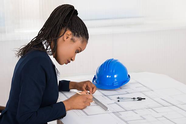 businesswoman drawing blueprint - arquitecta fotografías e imágenes de stock