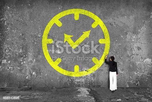 istock businesswoman drawing  clock on the wall 468340898