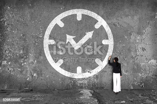 businesswoman drawing  clock on the wall