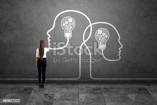 istock Businesswoman drawing human heads with light bulbs and gears 583827222