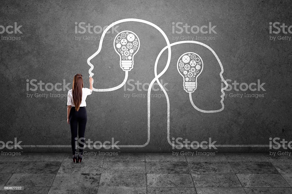 Businesswoman drawing human heads with light bulbs and gears stock photo