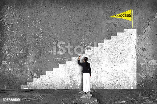 istock businesswoman drawing  ladder of success on the wall 526788599