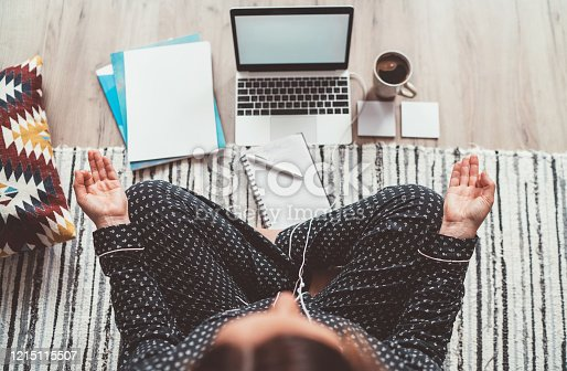 Businesswoman dressed in pajamas, listening earphones meditating with morning coffee with Gyan Mudra palm on floor office with laptop, papers top view shot. Distance work in quarantine time concept.