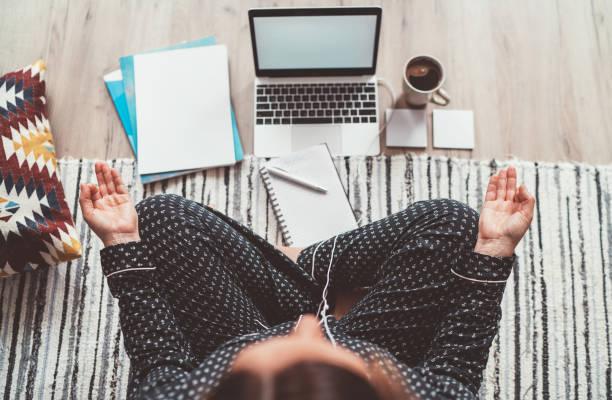 Geschäftsfrau in Pyjamas gekleidet, hören Kopfhörer meditieren mit Morgenkaffee mit Gyan Mudra Palm auf dem Boden Büro mit Laptop, Papiere Top View Schuss. Fernarbeit im Quarantänezeitkonzept. – Foto