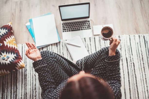 Geschäftsfrau in Pyjamas gekleidet meditieren mit Morgenkaffee mit Gyan Mudra Palmen. Auf dem Boden Büro mit Laptop, Papiere Top-View-Aufnahme. Fernarbeit im weltweiten Quarantänezeitkonzept. – Foto