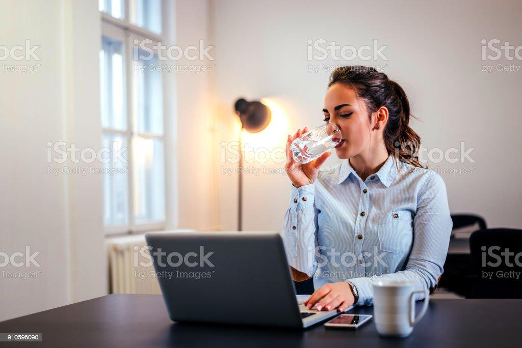 Geschäftsfrau, trinken ein Glas Wasser an ihrem Schreibtisch im Büro. – Foto