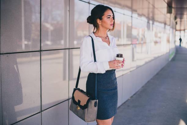 geschäftsfrau kaffeetrinken vor ihrem büro - outfit vorstellungsgespräch stock-fotos und bilder