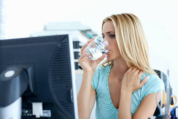 geschäftsfrau trinkwasser auf schreibtisch - arbeit in münchen stock-fotos und bilder