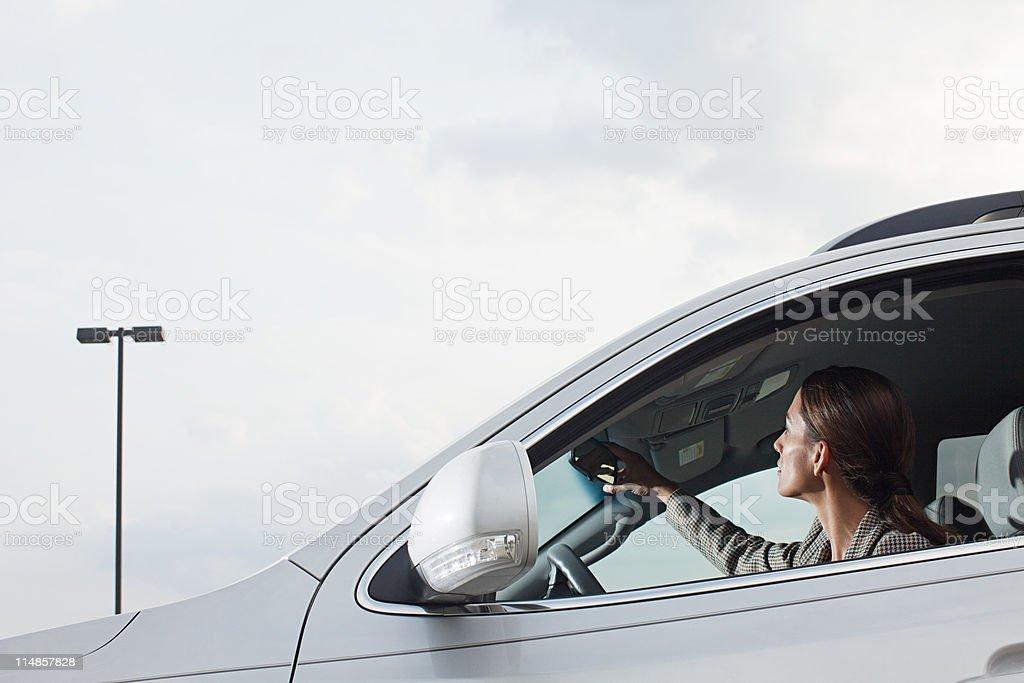 Empresária de carro, ajustando espelho retrovisor - foto de acervo