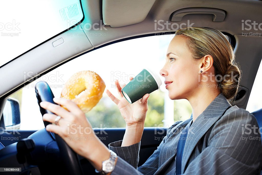 Businesswoman Driving to Work and Having Breakfast. stock photo