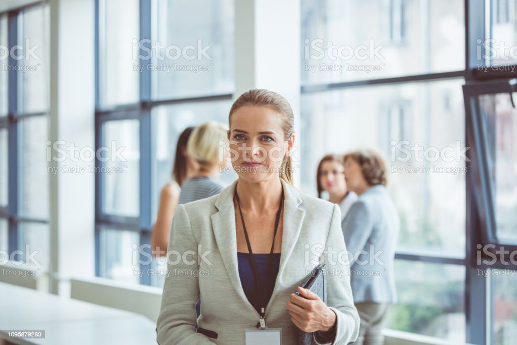 Businesswoman during break in seminar Portrait of beautiful businesswoman standing in the office lobby with colleagues in background during a break in seminar Adult Stock Photo