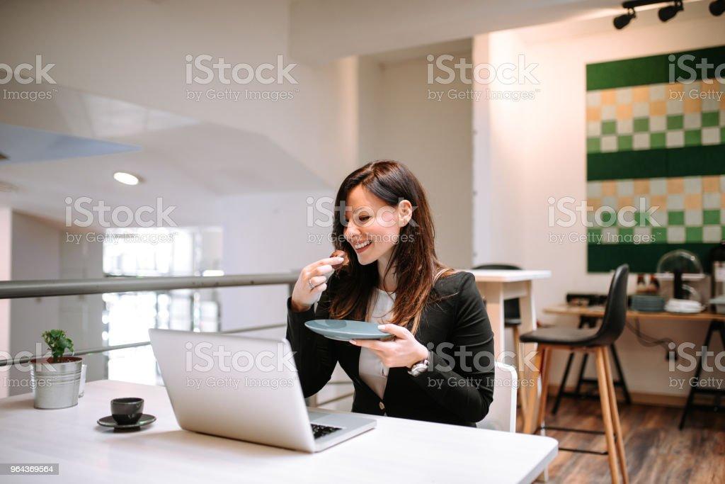 Empresária comendo bolinho enquanto olha para a tela do laptop. - Foto de stock de Adulto royalty-free
