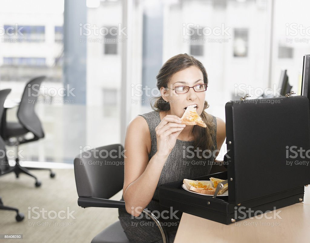 Businesswoman eating pizza from briefcase stock photo