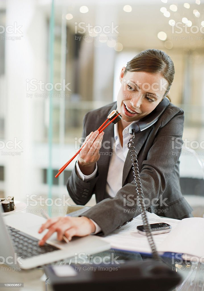 Businesswoman eating sushi and working at desk royalty-free stock photo