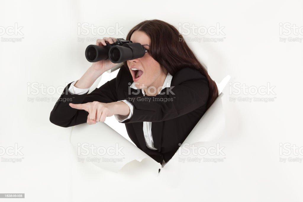 Businesswoman emerging through hole using binoculars royalty-free stock photo