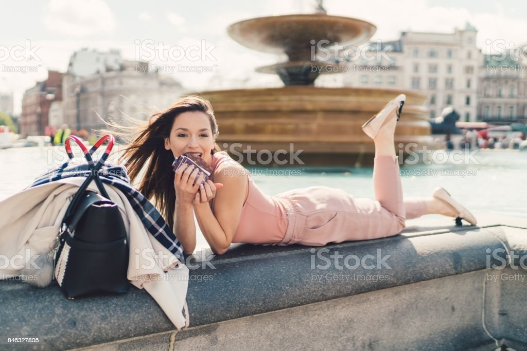 Businesswoman enjoying a chocolate bar at the fountain stock photo