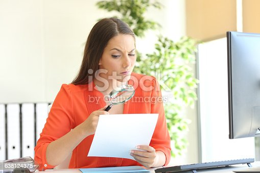 istock Businesswoman examining a contract meticulously 638124378